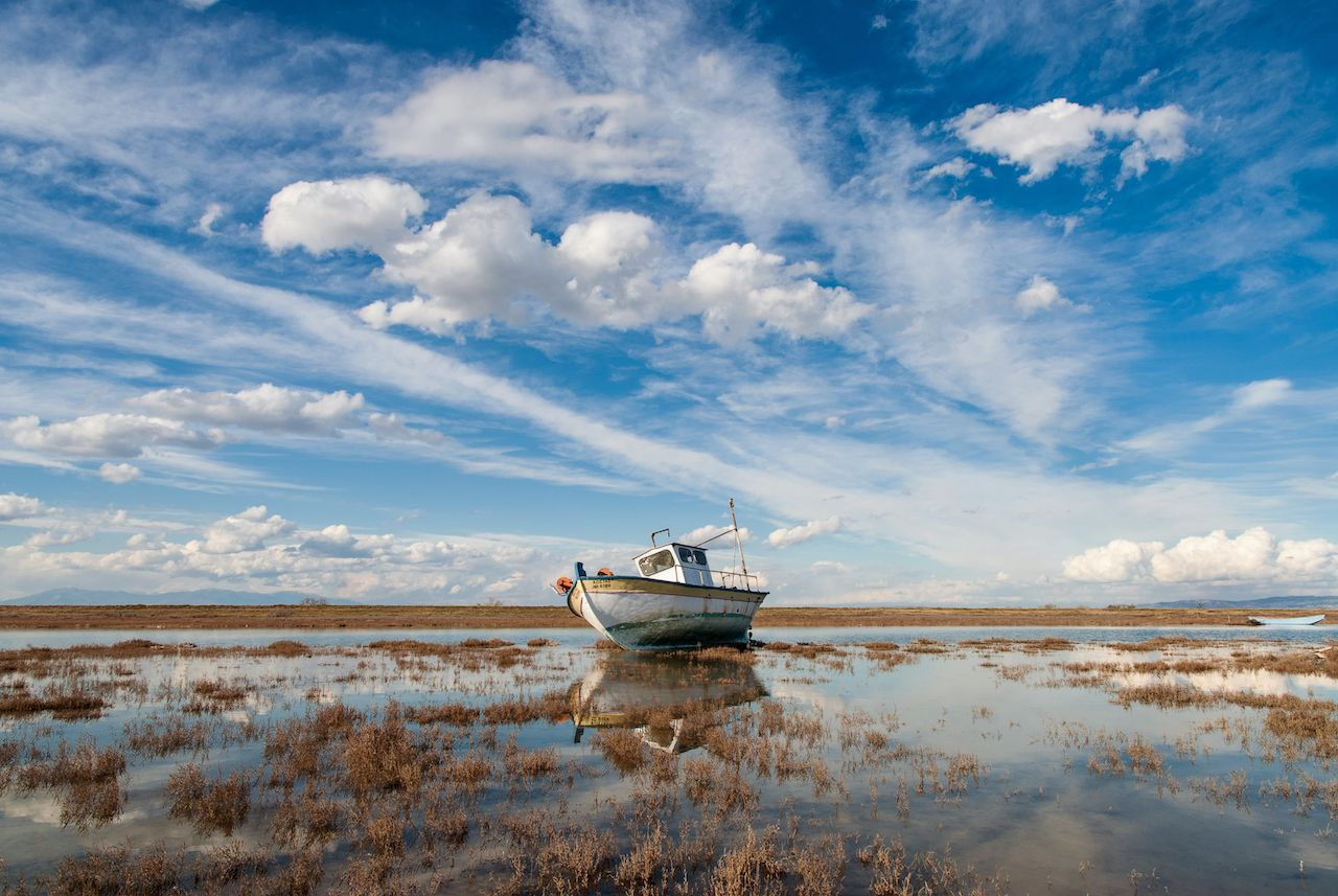 Landscape with traditional wooden boat in Axios Delta near Thessaloniki, Greece