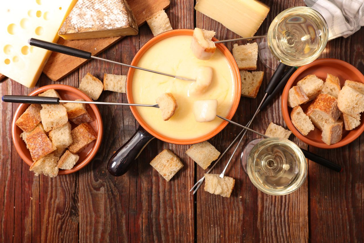 Pot of fondue with bread and cheese on a table