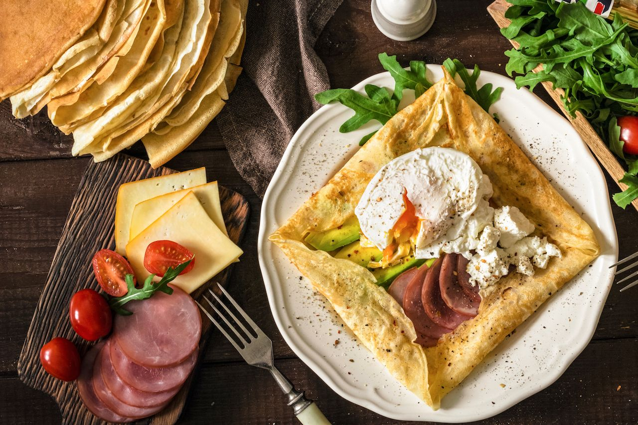 Crepe pancake with ham, avocado, soft white cheese and egg on white plate