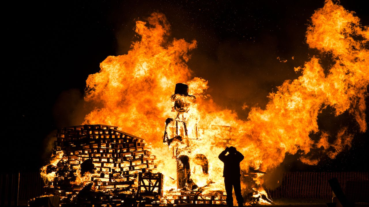 Man takes a picture during a bonfire the night of the fifth of November